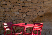 A tomato-red café table in the sun