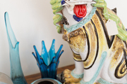 An antique foo dog amid midcentury glassware and ceramics