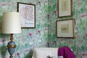 Vibrant wallpaper behind gold framed photos and white chair.