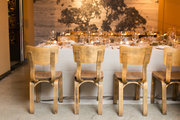 A neutral dining table with wooden dining chairs.