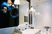 Black walls and monogrammed hand towels in a bathroom with a marble sink