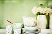 A floral-patterned tea set beside a pitcher of flowers