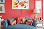 A blue couch paired with red walls decorated with art