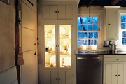 A built-in china cabinet with glass doors in a white kitchen