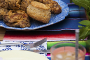 Fried chicken and biscuits and tacos on an alfresco dinner table