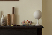 A sculptural lamp sits atop a mantel in a living room.