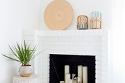 A contemporary white fireplace with boho accents.