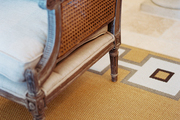 A caned chair layered atop a natural-fiber rug with a geometric border