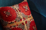A velvet blue chair with a bright red pillow