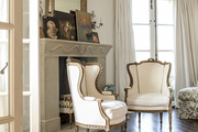 A pair of stately armchairs in front of a mantle in a master bedroom