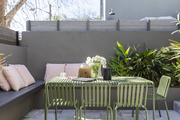A light green outdoor patio table with built-in bench seating surrounding the set up.