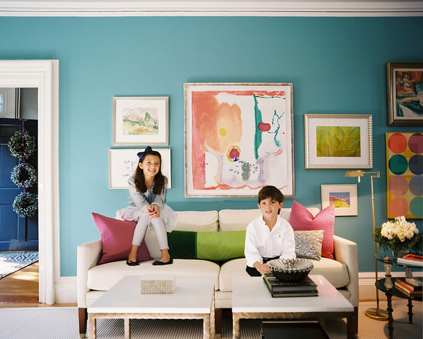 Living Room - Children seated on a white couch backed by a gallery wall of art