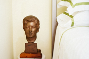 A bust on a white faceted bedside table