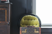 A lime green tufted chair with a vintage Vuitton carrying case