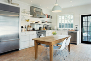 A wooden table and molded-plastic chairs in a white kitchen with brick flooring