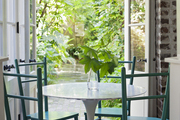 A tulip-style table surrounded by green chairs