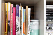 A striped mug supports a shelf of books