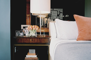 A transparent lamp and framed photos atop a wooden bedside table