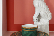 Malachite dishes by Dior and a ceramic foo dog sit in a bookcase.