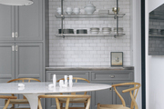 A kitchen with gray cabinetry, open shelving, white subway tile, a Saarinen table, and Hans Wegner Wishbone Chairs