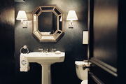 A bathroom with gray walls, a pair of sconces, and a white pedestal sink