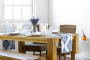 A wooden dining table set with dried lavender and a blue-and-white runner