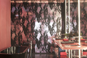 Large-scale patterned wallpaper in a black-and-pink bathroom