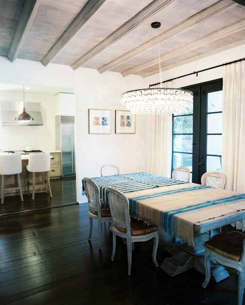 Chandelier suspended above a dining table and set of cane back chairs