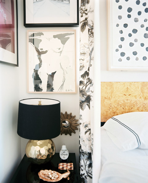 Michelle Adams - A grouping of art above a black bedside table