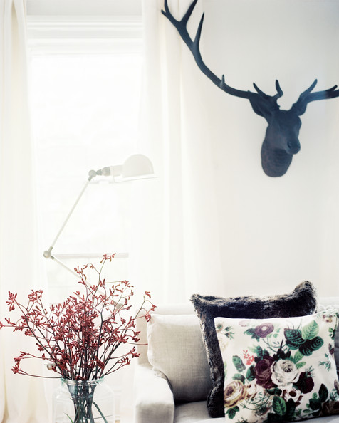 Michelle Adams - An iron stag head above a linen couch with floral pillows