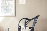 A black wicker chair with white cotton fringe.