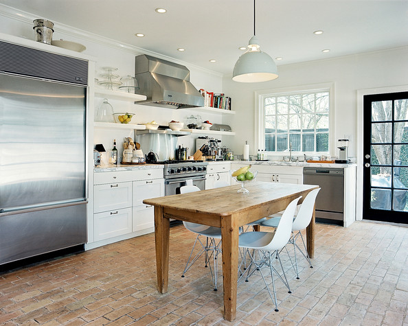 Modern - A wooden table and molded-plastic chairs in a white kitchen with brick flooring
