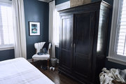 A bedroom with blue walls and a wooden armoire.