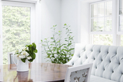 A feminine breakfast nook with a tufted banquette, crystal chandelier, and round, wood pedestal table