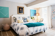 An oil portrait hung above a white upholstered bed outfitted with a mix of patterns