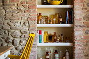A kitchen nook with white open shelving and brick walls