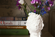 A vase of flowers and a stack of books on a chest of drawers