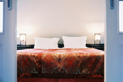 Small-scale checkered carpeting in a room with red patterned bedding