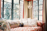 A daybed with patterned pillows arranged beside windows