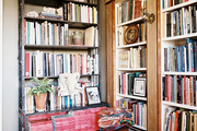 A black bookshelf beside built-in bookcases flanked by faux columns