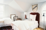 A pair of twin beds and a striped rug in a guest bedroom