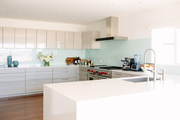 A sleek all-white kitchen with seafoam green backsplash.