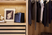 A sectioned closet featuring open wood hanging rack and storage drawers