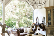 An equestrian tack room with rustic, leather accents and a chandelier