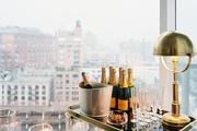 Champagne set on a tray table surrounded by walls of windows