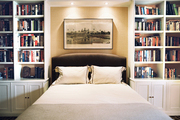 An upholstered bed flanked by white built-in bookcases