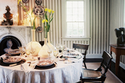 A table set with transferware in a dining room with striped walls