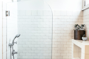 A bathroom with white subway tile and a glass door.