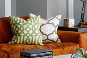 Patterned throw pillows atop low-back orange couch.