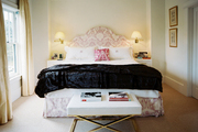 An X-base bench at the foot of a pink upholstered bed with monogrammed linens